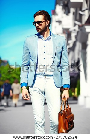 High fashion look.Young stylish confident happy handsome businessman model  in suit cloth lifestyle in the street in sunglasses with bag - stock photo