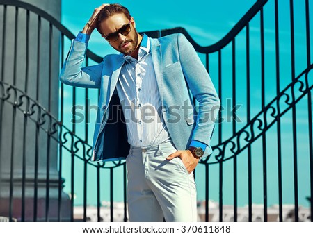 High fashion look.Young stylish confident happy handsome  businessman model man in blue suit cloth lifestyle in the street behind sky in sunglasses