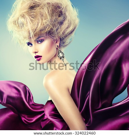 High fashion model girl portrait. Glamorous beauty woman with Updo hairstyle and bright makeup dressed in violet silk flying dress. Glamour Lady posing in studio - stock photo