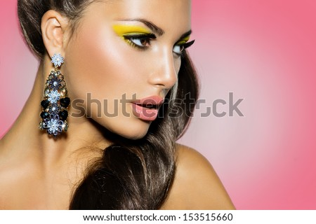 High Fashion Model Girl Portrait over Pink Background. Creative Make up. Yellow Eyeshadow, Ponytail Hairstyle, Trendy Earrings. Perfect Skin - stock photo