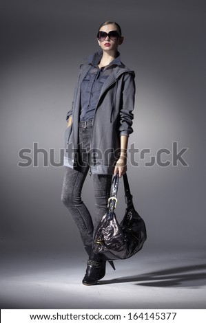 High fashion model in fashion dress wearing sunglasses with bag  posing in the studio