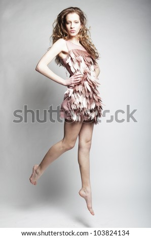 High fashion model jumps in studio - stock photo