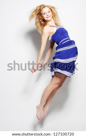 High fashion model jumps in studio - stock photo