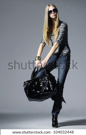 High fashion model wearing sunglasses with bag posing in the studio - stock photo