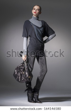 High fashion model wearing sunglasses with bag posing in the studio