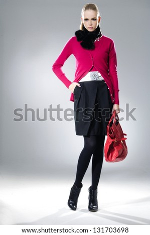 High fashion model with red bag posing on light background - stock photo