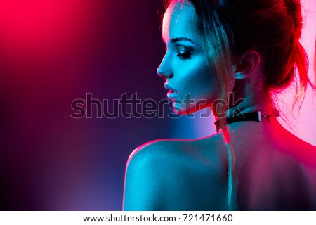 High Fashion model woman in colorful bright lights posing, portrait of beautiful  girl with trendy make-up. Art design, colorful make up. Over colourful vivid background.