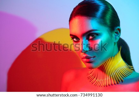 High Fashion model woman in colorful bright lights posing, portrait of beautiful sexy girl with trendy make-up. Art design, colorful make up. Over colourful vivid background. Night club dancer.