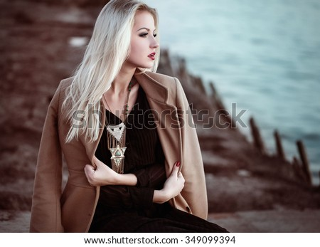 High fashion photo of elegant woman in black long dress, coat and stylish necklace in boho style. - stock photo