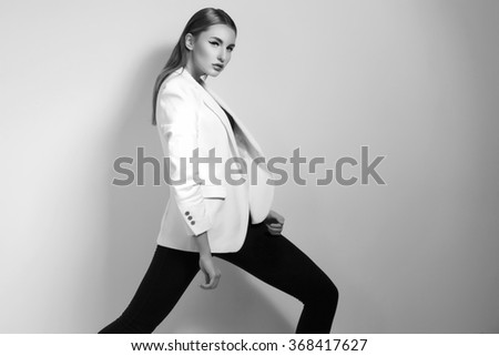 High fashion photo of young beautiful model in trendy white jacket and black pants. Vogue style. Copy space.