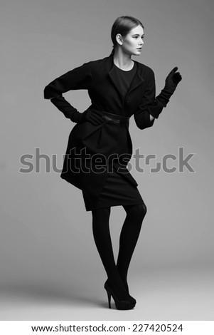 high fashion portrait of elegant woman in black coat.  Black and White image - stock photo