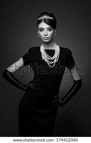 high fashion portrait of elegant woman in black dress and gloves. Black and white shot - stock photo