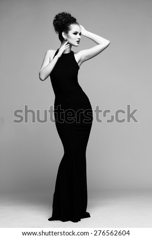 high fashion portrait of elegant woman in long black dress. Black and white studio shot - stock photo