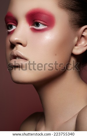 High fashion portrait of expression young woman with bright magenta eye make-up, pale full lips and smooth clean skin. Close-up macro beauty shoot on red background  - stock photo
