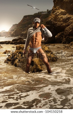 High fashion portrait of sexy male model in stunning beach setting - stock photo
