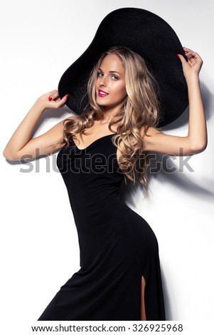 High fashion shot of blonde woman with curly hair in black hat and stylish elegant evening dress posing on white studio background.Red lips - stock photo