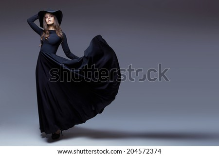 High fashion shot of elegant woman in a hat and long fluttering dress.   - stock photo