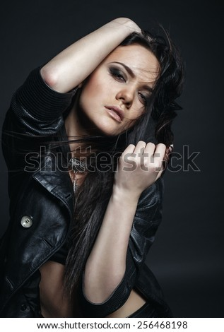 High fashion vogue girl in the black leather dress in the studio