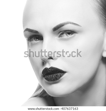 High fashion vogue style, manicure, cosmetics and make-up. Studio portrait of female caucasian young blonde model with black lipstick isolated on white background. Black and white