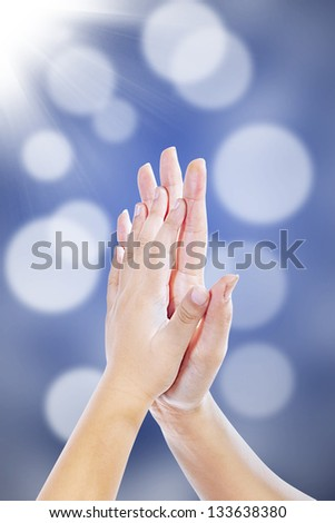 High five hand gestures between mother and son on blur background - stock photo