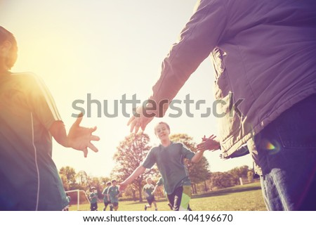 High Five line after a child's soccer game, lens flare, shot into the sunlight, Instagram image - stock photo