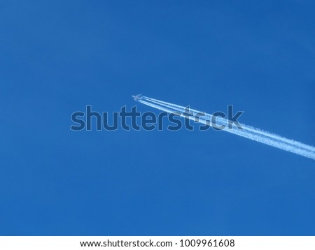 High flying plane in the clear blue sky. Jet airplane with trail of fuel