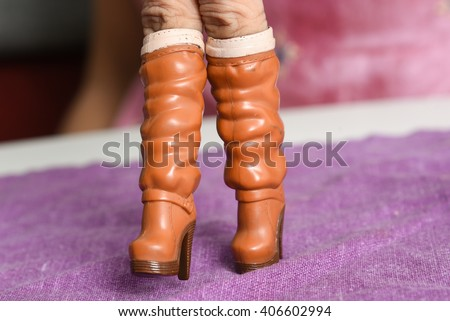 High heel boots, hand finger walking with shoe, walking hand, Stylish leather boots, elegant female high boots, girl heel boots, kid playing barbie boots, girls, ladies brown boots, women boots   - stock photo