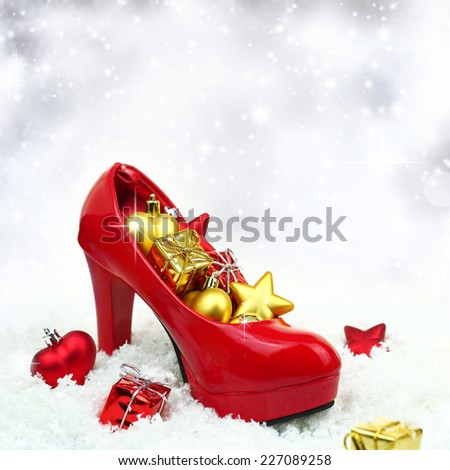 High heel shoe with christmas ornaments on snow - stock photo