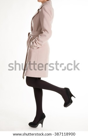 High heels and light coat. Black shoes with beige coat. Dark pantyhose and cashmere coat. Woman's conservative style. - stock photo