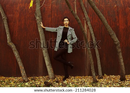 High heels concept. Fashion full length portrait of beautiful brunette in trendy casual clothes posing in autumn park over rusty metal background. Urban style. Outdoor shot - stock photo