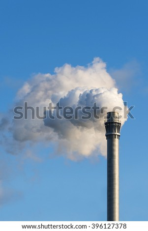 high industry chimney with clouds of smoke against the blue sky with copy space, vertical