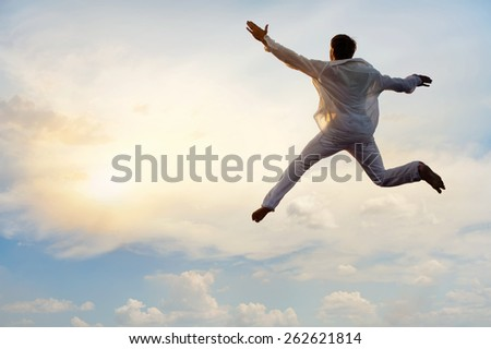 High jump of man on background of bright sunny sky with white clouds - stock photo