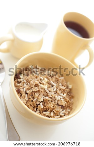 High key image of a healthy wholesome breakfast with a bowl of muesli with a jug of milk and mug of freshly brewed filter coffee - stock photo