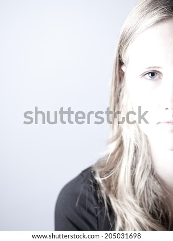 High key image of a young teenage girl looking sad or depressed over a gray background - stock photo