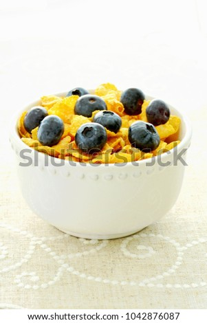 High key image of crunchy golden corn flakes with fresh juicy blueberries in vertical format and shot in natural light