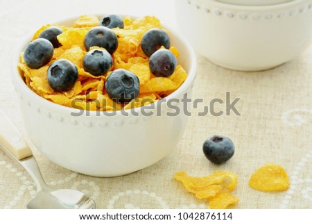 High key image of Crunchy golden corn flakes with sweet juicy blueberries in horizontal format and shot in natural light