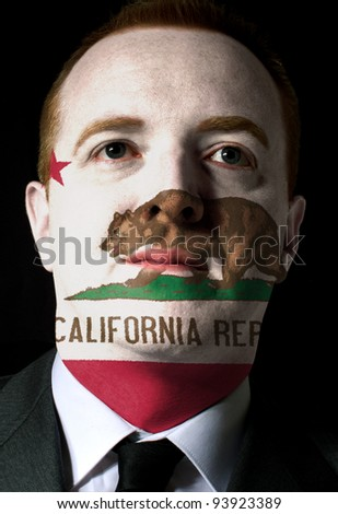 High key portrait of a serious businessman or politician whose face is painted in american state of west california flag - stock photo