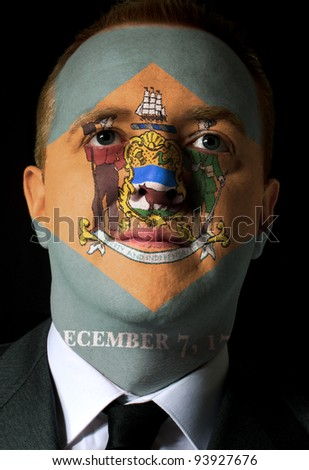 High key portrait of a serious businessman or politician whose face is painted in american state of west delaware flag - stock photo