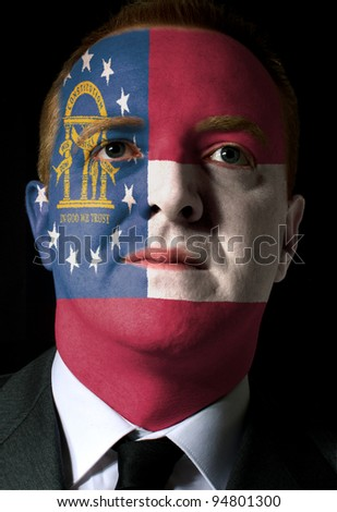 High key portrait of a serious businessman or politician whose face is painted in american state of georgia flag