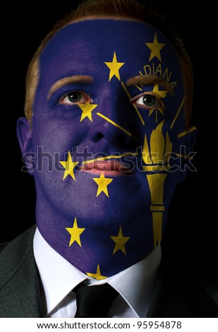High key portrait of a serious businessman or politician whose face is painted in american state of indiana flag - stock photo