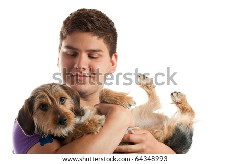 High key portrait of a young man holding a cute mixed breed borkie dog isolated over white. Shallow depth of field with focus on the mans face.