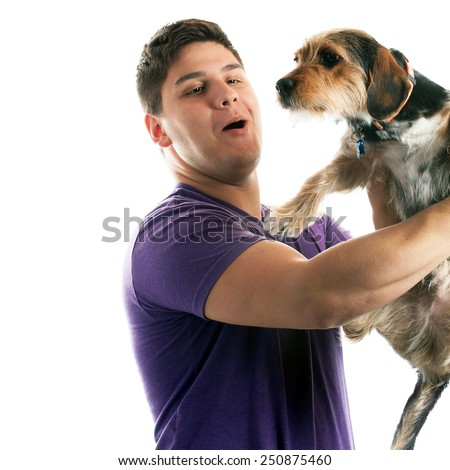 High key portrait of a young man holding a cute mixed breed dog isolated over white.  - stock photo