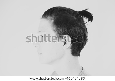 High key portrait of a young man with a bun.