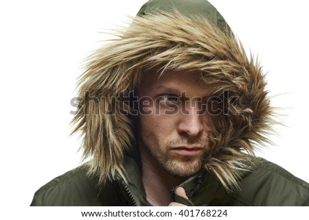 High key studio portrait of young adult caucasian model wearing winter coat with hood. - stock photo