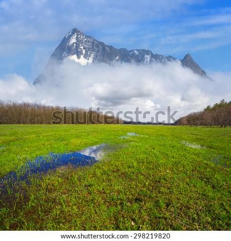 high mount beyond a green fields - stock photo