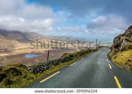 high mountain Ireland Scotland road narrow nature pass cloudy blue sky - stock photo