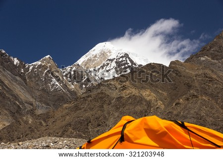 High Mountain Peak and Cropped Orange Tent Snowbound Summit Rock Ridge Blue Sky and Cloud Blown Away from Top of Mountain by Strong Wind - stock photo