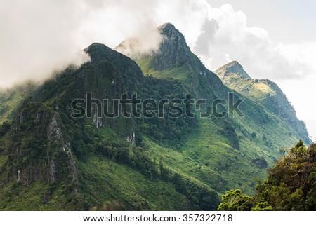 High mountain ridge in thick fog - stock photo