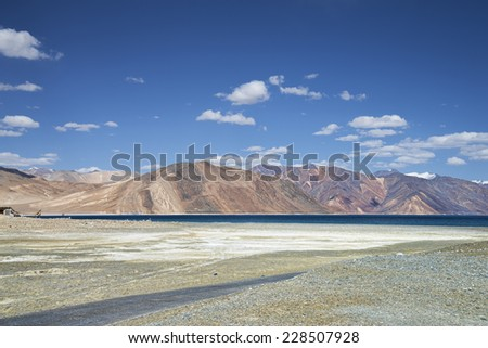 High mountain road beside of deep blue lake - stock photo