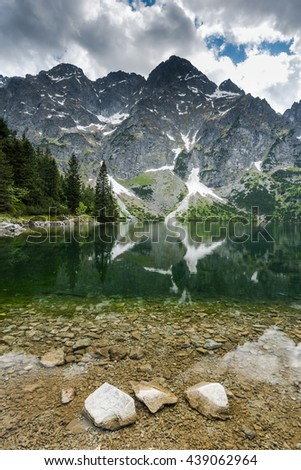 High mountain summit reflect in alpine lake cristal clear water - stock photo
